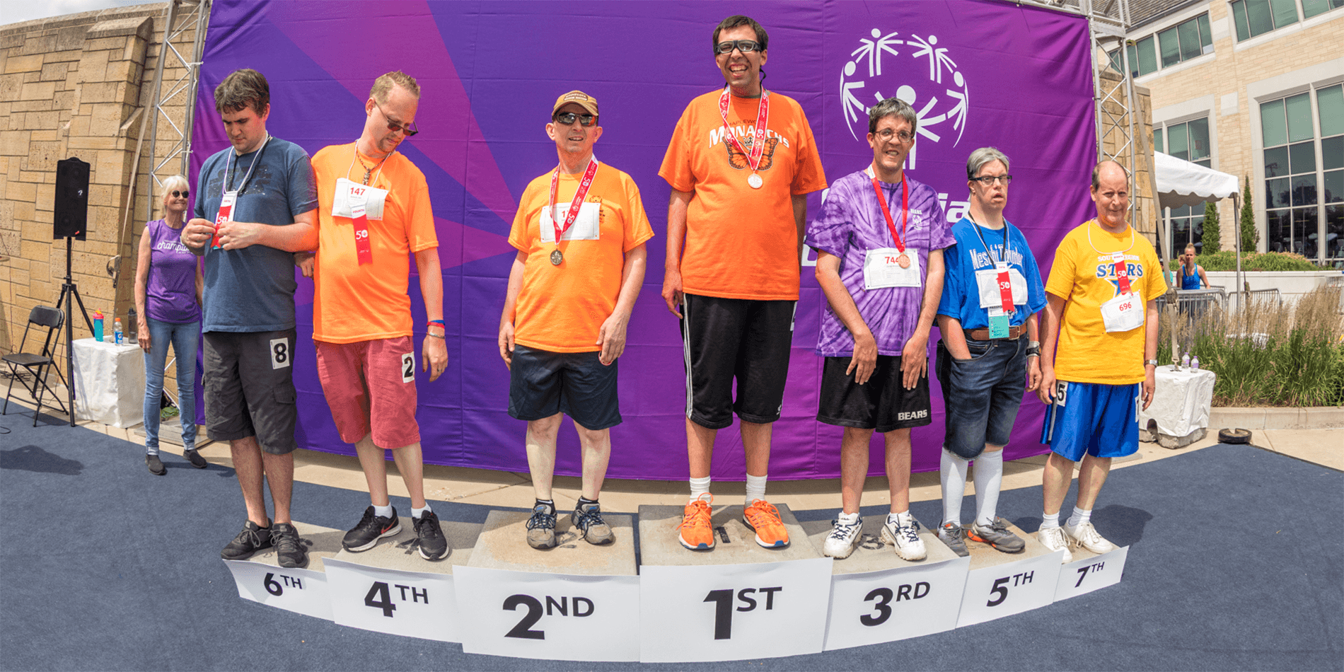 Special Olympics Minnesota athletes standing on podiums smile and show off their medals