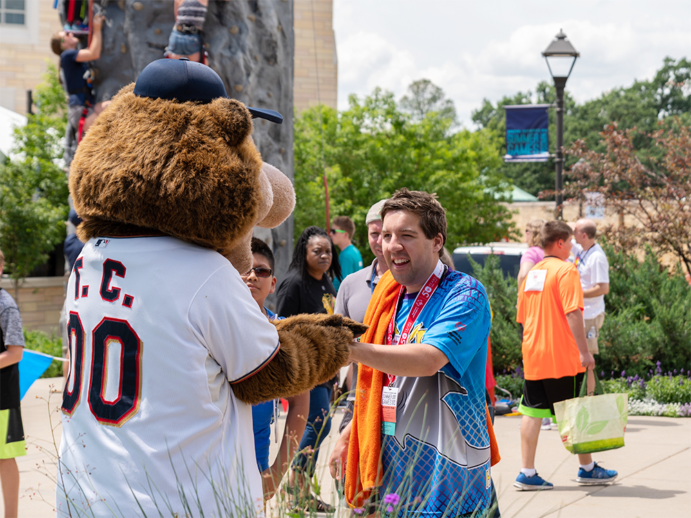 A Special Olympics Minnesota athlete shakes hands with Twins mascot T.C. Bear