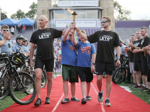 Two Special Olympics Minnesota athletes and two Law Enforcement Torch Run officers carry the Flame of Hope into Celebration Ceremonies