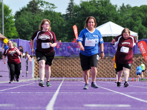 Four Special Olympics Minnesota track & field athletes run down the track